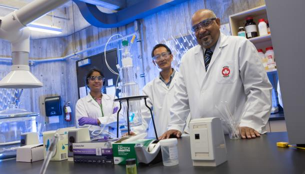 Dr. Suresh Narine standing at a lab desk with 2 students in white lab coats, wearing goggles and smiling at the camera