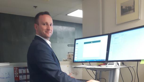 Stephen van der Werf standing in front of two computer screens, working away while wearing a a suits