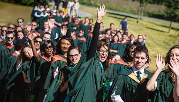A large group of students walking along a green lawn in their cgreen Trent University convocation gowns, smiling and waving at the camera in the summer sun