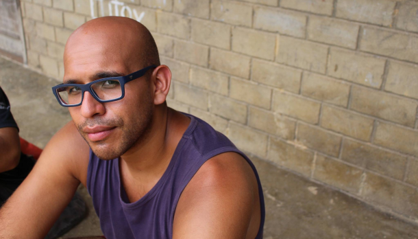 Jose Sanchez sitting on cement floor against brick wall while wearing a purple tank top and looking up