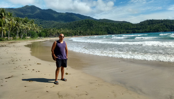 Jose Sanchez standing in front of a beautiful beach surrounded by mountains in the Philippines