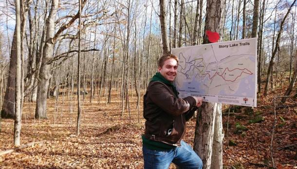 Spencer Walker stands smiling in front of map of Stony Lake Trails in the woods on a sunny autumn day