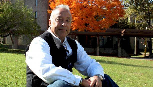 Dr. Dan Longboat sits outside Champlain College on a sunny autumn day