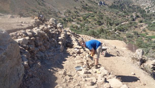 Brendan Bell-Earle cleans the top of an exposed wall at an archaeological dig in Crete on a sunny summer day