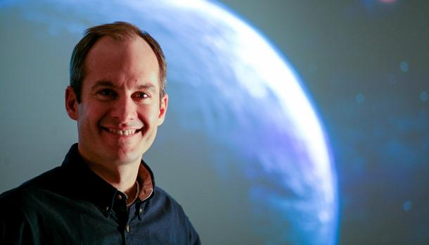 Dr. David Patton smilig at the caerma in front of a picture of a planet in space
