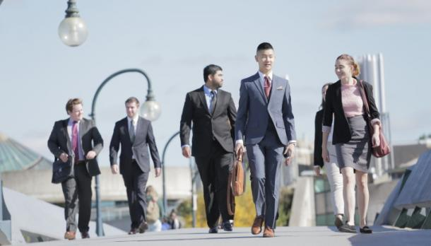 couple of business students walking across the Faryon bridge while wearing formal clothing