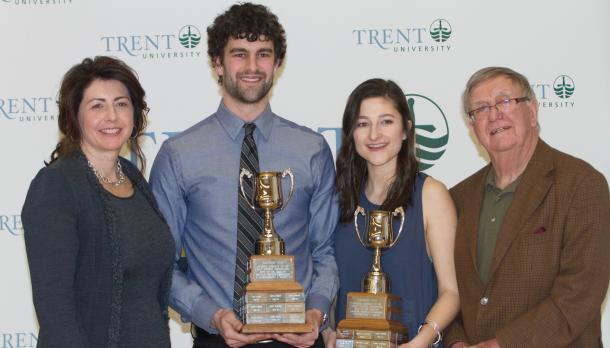 Leah Ogilvie and Griffin Williams with two other adults holding trophies and smiling in front of a Trent banner.