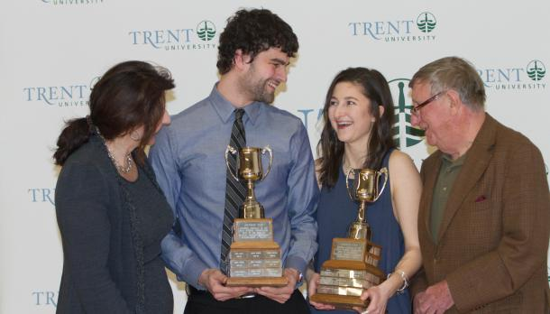 Leah Ogilvie and Griffin Williams with two other adults holding trophies and laughing in front of a Trent banner.