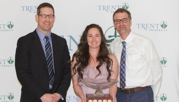 Abigail Adair with two other adults holding trophies and smiling in front of a Trent banner.