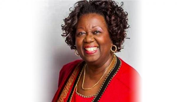 The Honourable Dr. Jean Augustine smiling at the camera against a white background, wearing a red dress shirt and gold necklace