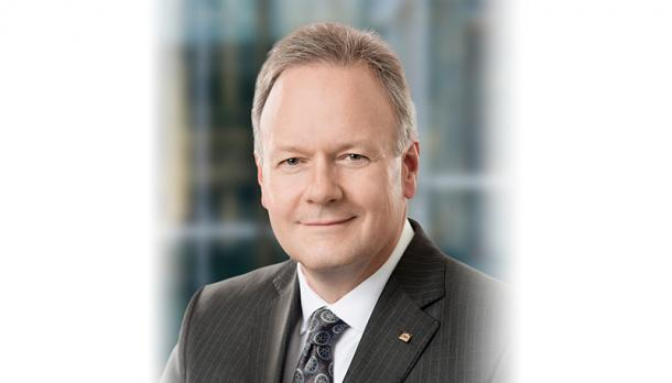 Governor Dr. Stephen Poloz smiling at the camera in a grey business suite in front of a blurry city scape