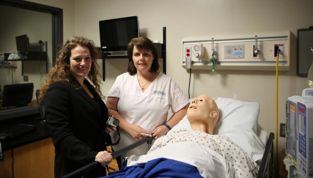 Two women standing beside a nursing simulation dummy in the nursing lab at Trent University
