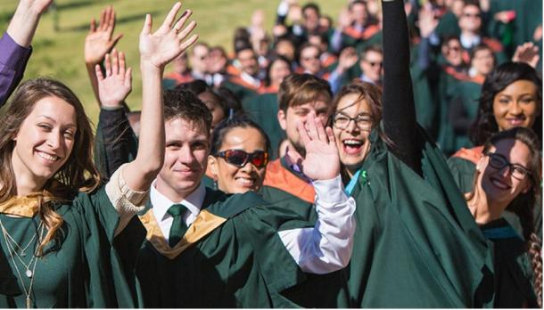 students in convocation gowns waiving