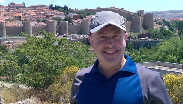 Dr. David Sheinin smiles in while standing on a hill beside a city