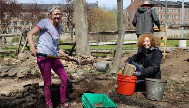 2 girls smiling and holding shovels in the dirt in front of Trent University