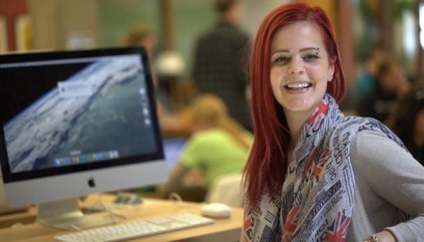 Young woman, sitting at Mac, looking at camera