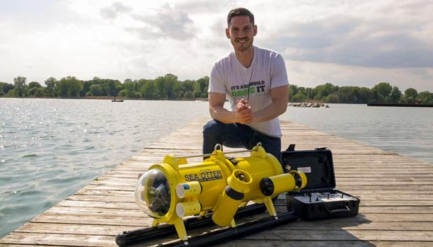 Ryan Cant smiling at the camera on a dock in front of his creation