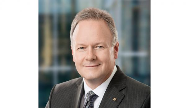 Stephen poloz wearing a dark suit, smiles at camera