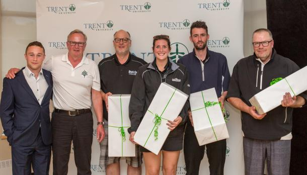 students and coaches pose after winning prizes in golf tournament
