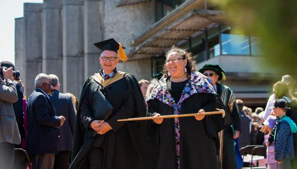 David Newhouse stands beside indigenous graduate on convocation day