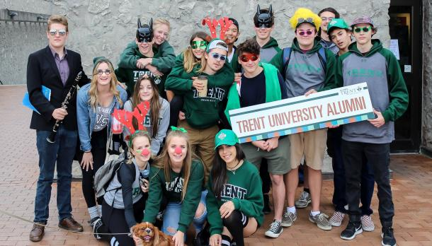 Group photo of alumni wearing silly hats and noses at homecoming