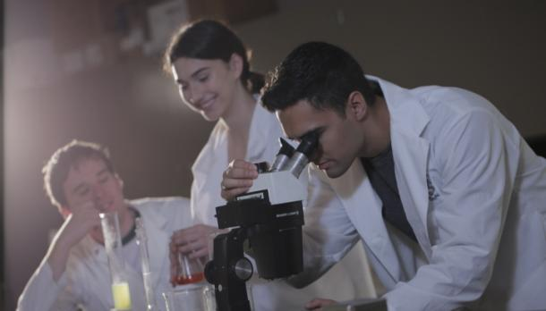 Students work in a science lab with beakers and a microscope