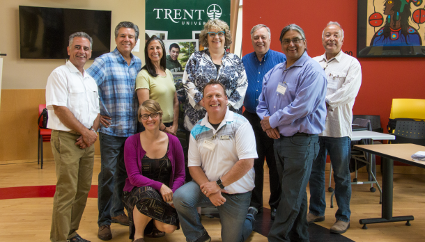 A group of people in the Gathering Space at Trent University facing the camera and smiling