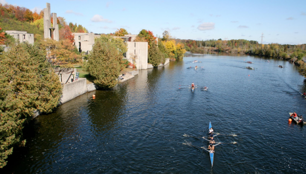 Several boats row in front of Champlain College