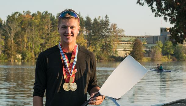 Trevor Jones standing in front of the Otonabee River holding a rowing oar