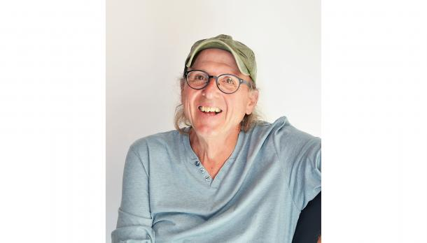 Dr. Stephen Brown, English Professor smiling to camera while wearing a blue shirt and a green cap