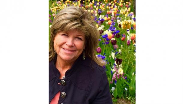Sue Graham Parker smiling in front of garden