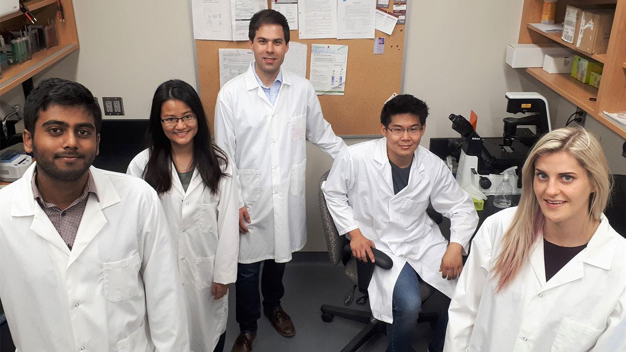 Robert Huber alongside Graduate and Undergraduate students wearing their lab coats.