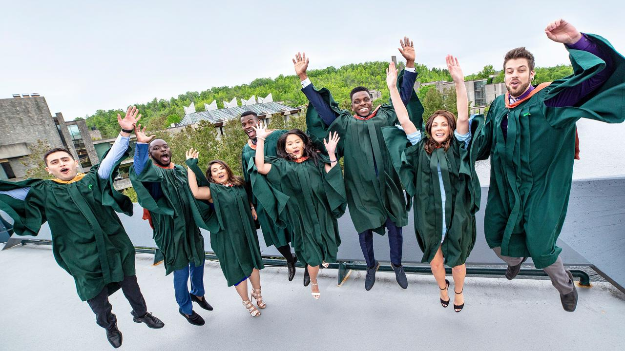 Students at convocation jumping with their hands in the air.