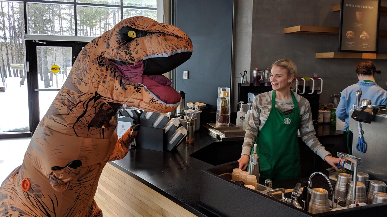 Dinosaur costumed person  at counter with smiling Starbucks employee in Trent's Student Centre