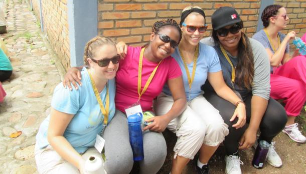 Second year nursing students in Hondura smiling to the camera while sitting next to a brick wall