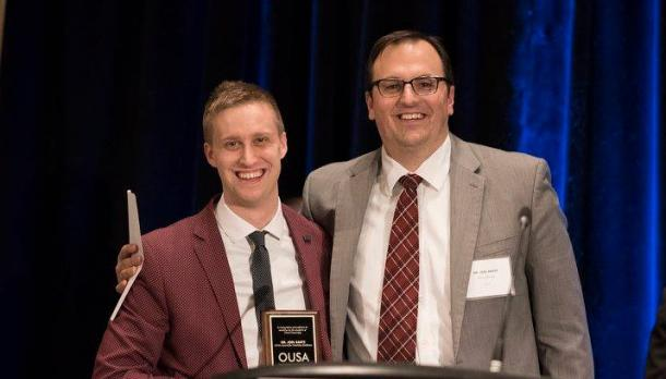 Professor Joel Baetz standing beside another male presenter in front of a podium doling an award