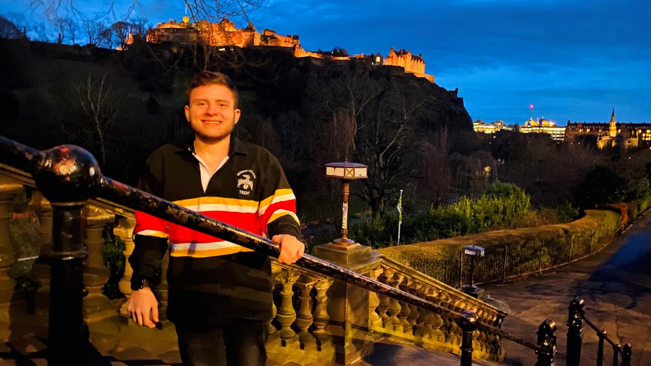 Third-year exchange student Theo Williamson (Gzowski College) poses in front of the Edinburgh Castle, in Scotland, wearing his Gzowski College apparel from Trent University.
