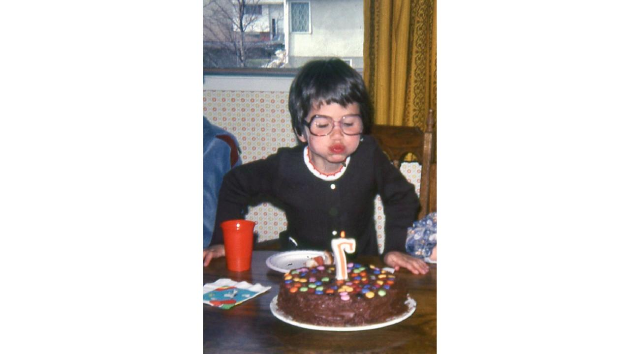 Sally Chivers blowing out the candles on her birthday cake at the age of 7.