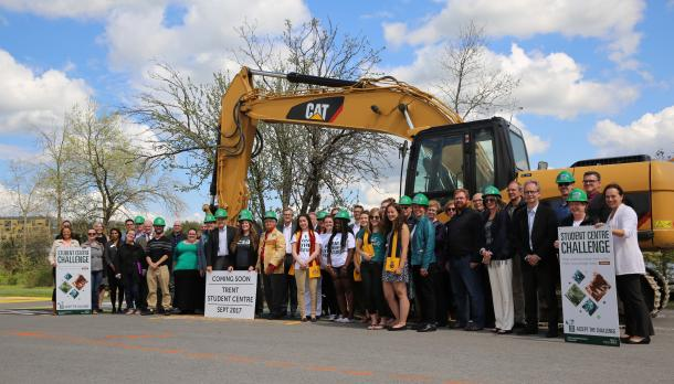 A group of staff and fcaulty gathered in front of a digging machine in the parking lot, smiling at the camera