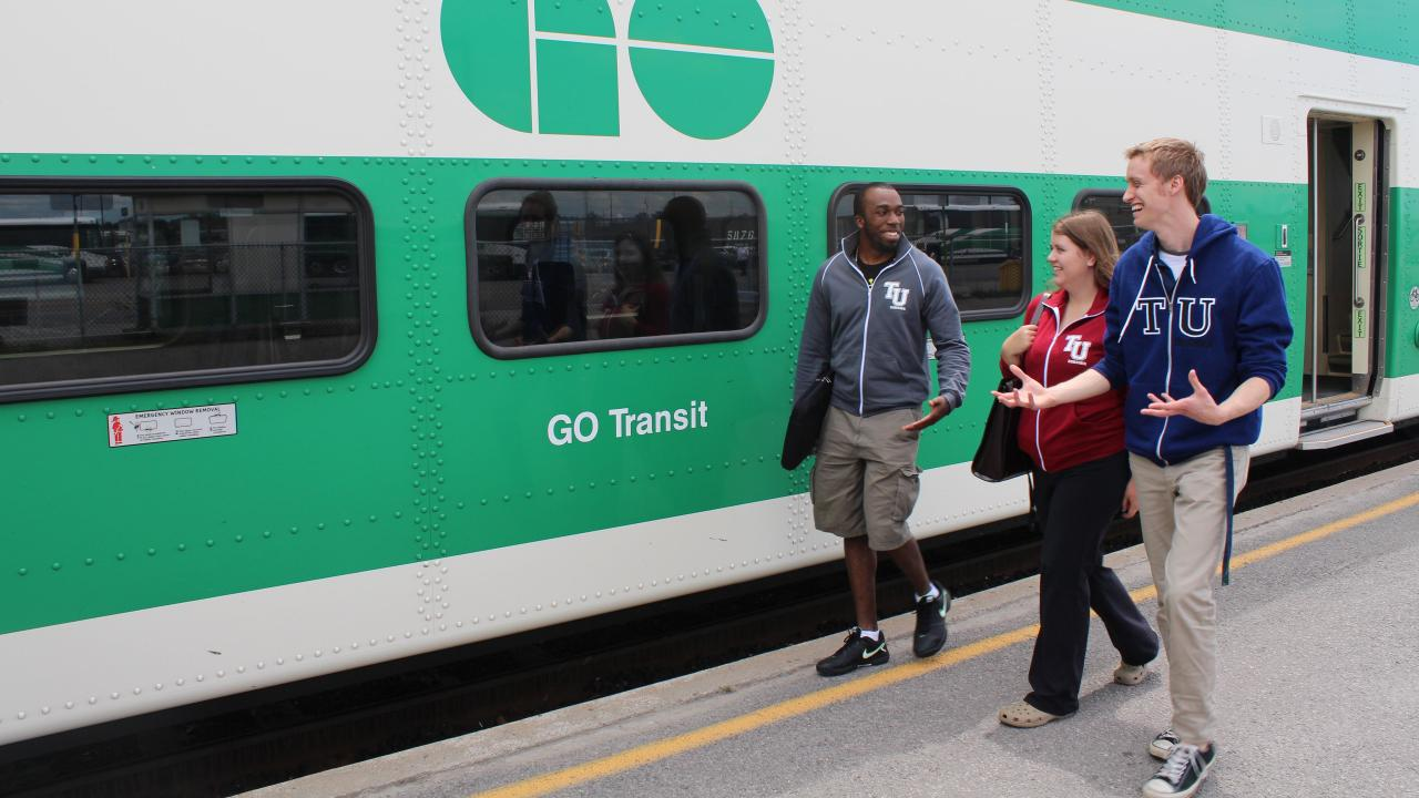 Trent students walking on the platform at the Oshawa GO station. Stationary train in background.