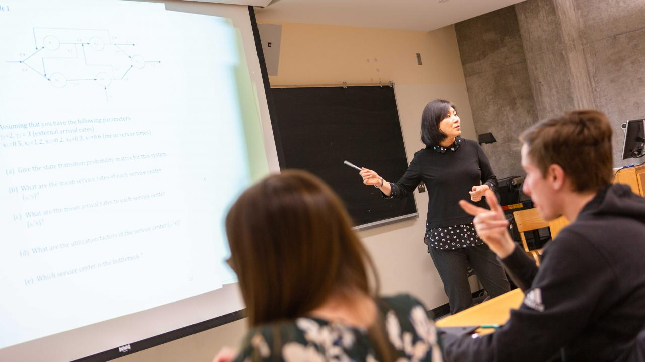 Students in a classroom, professor pointing to lecture materials on projector screen