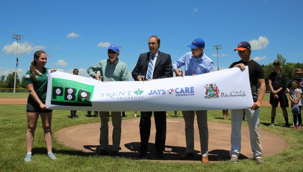 Dr. Leo Groarke and Peterborough mayor standing on the mound cutting a banner that launches the new baseball field