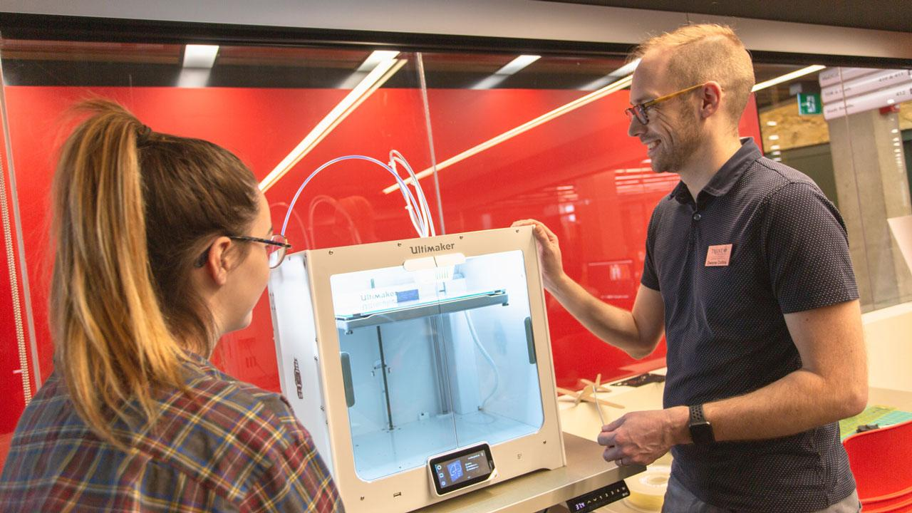 Dwayne Collins, Trent University's digital scholarship and innovation librarian shows a student the 3D printer located in Bata library.
