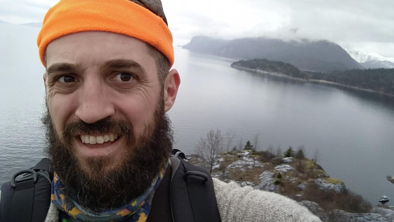 A selfie of Professor Aaron Shafer standing in front of a lake, smiling at the camera