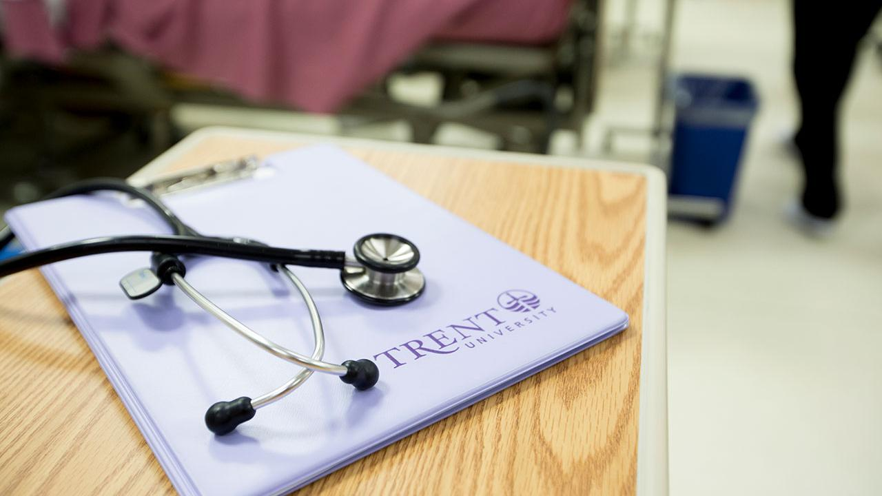 A Stethoscope sits on top of a Trent Nursing clip board