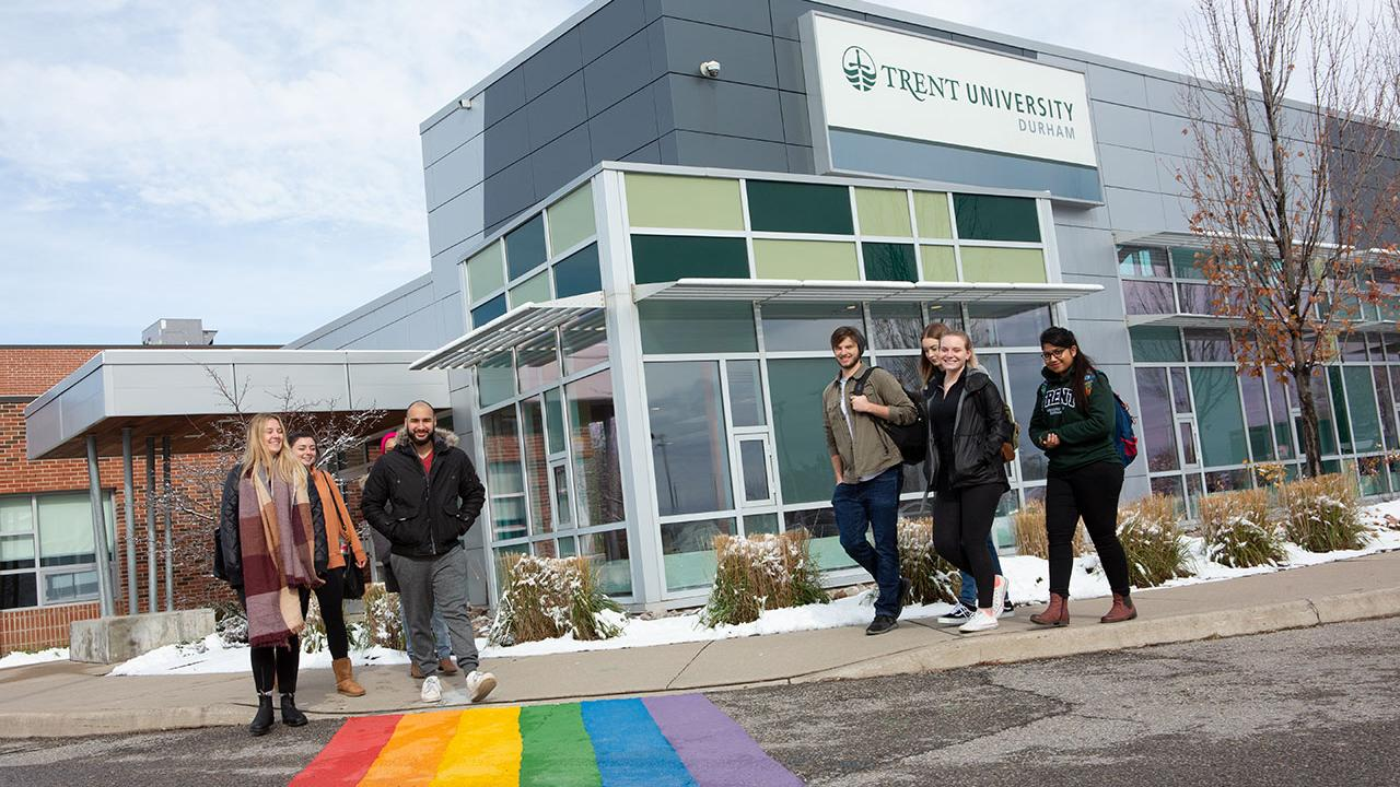 Students walking outside of Trent Durham and smiling at the camera