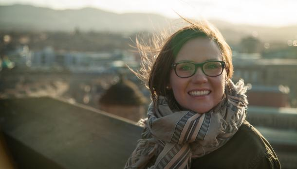 Heidi Dienesch smiling to camera wearing her glasses in front of few building at sunset