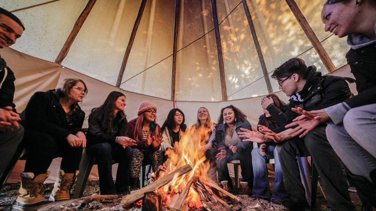 Students gathered around fire inside tipi