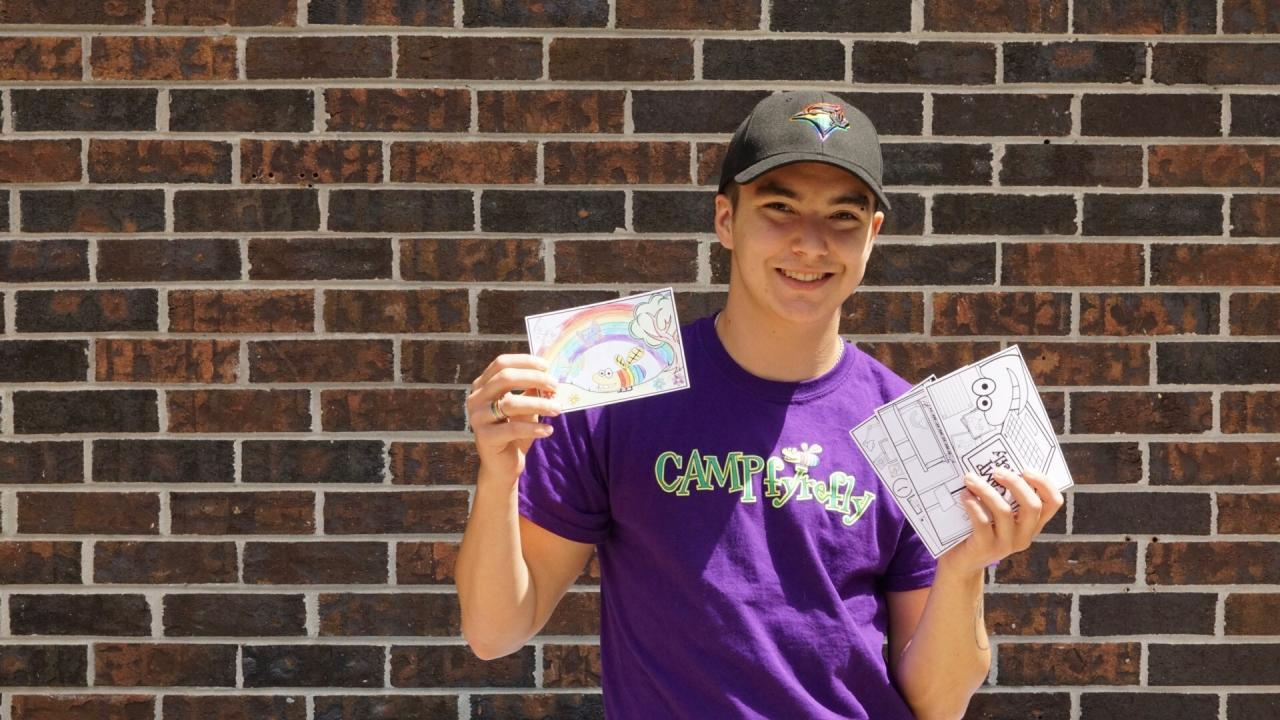 Former camper - now Youth Leader – Kris posing with fYrefly postcards he designed for campers.