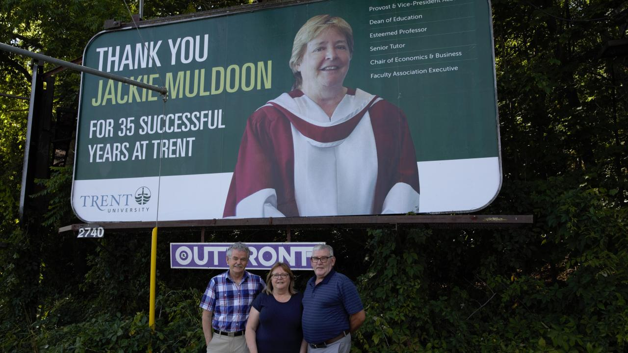 President Leo Groarke with Jackie and Joe Muldoon in front of a thank you billboard